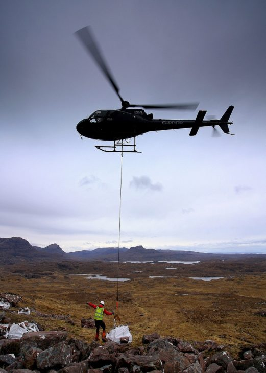 The helicopter lifting a bag of stone from the boulder field. Photo © Chris Goodman.
