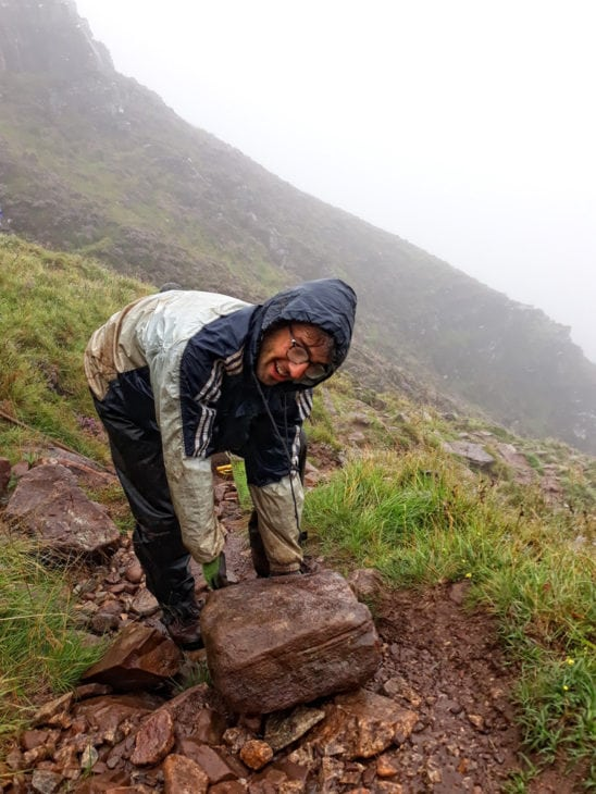 Ewan manoeuvres a big stone into position. Photo © Chris Puddephatt.