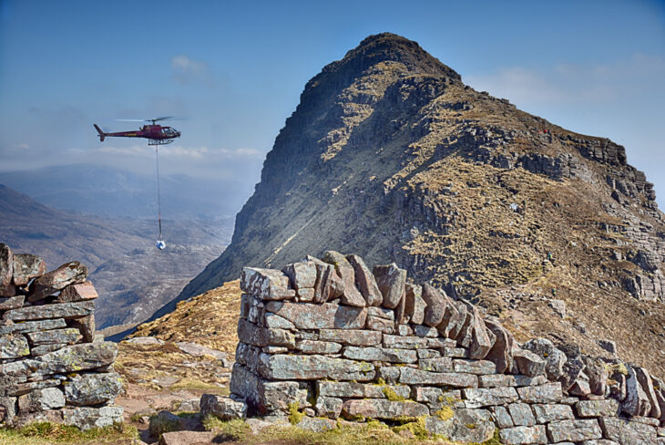 A helicopter delivers bags of stone to the ridge of Suilven © Chris Puddephatt