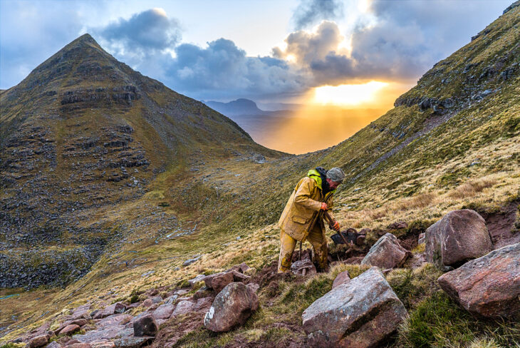 worker laying stone on Quinag path